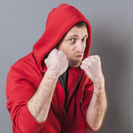 bossy: male fighting concept - bossy middle age male rapper showing his fists for sign of violence or bullying attitude,studio shot