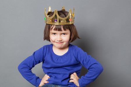 corona de reina: concepto de ni�o mimado - la sonrisa del ni�o preescolar con corona de oro en la cabeza que pone las manos en las caderas de confianza peque�o rey mollycoddled o met�fora reina, tiro del estudio Foto de archivo