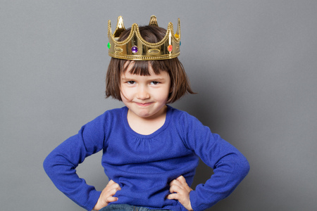 spoiled kid concept - smiling preschool child with golden crown on head putting hands on hips for confident mollycoddled little king or queen metaphor,studio shot