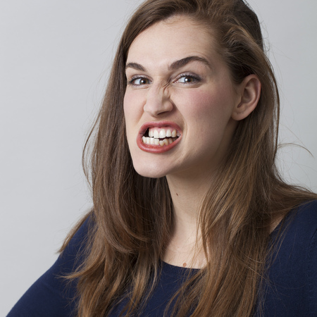 female anger concept - angry beautiful 20s girl grinding her teeth threatening someone,showing aggressiveness,closeup in studio