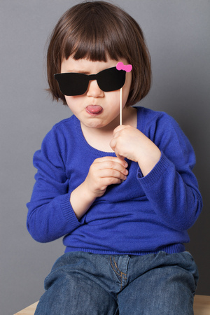 mocking: fun kid glasses concept - spoiled female preschool child holding fake black sunglasses for mocking movie star,studio shot