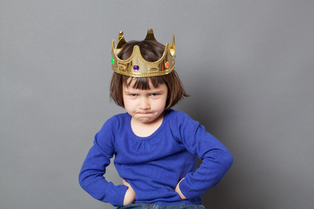 spoilt kid concept - adorable preschool child with golden crown on head putting hands on hips for confident mollycoddled little king or queen metaphor,studio shot