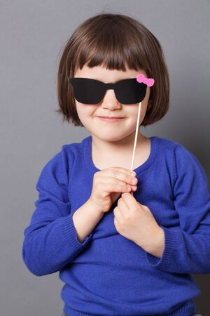 dressing up: fun kid glasses concept - smiling preschool child holding fake black sunglasses for playing like her mother,dressing up as lady,studio shot
