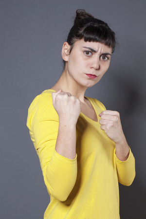 rebellion: female fighting concept - unhappy 20s woman showing her fists in the foreground for self-defense or rebellion,studio shot