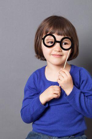 dressing up: fun kid glasses concept - smiling preschool child holding fake black round eyeglasses for playing like adult or dressing up as smart nerd,studio shot