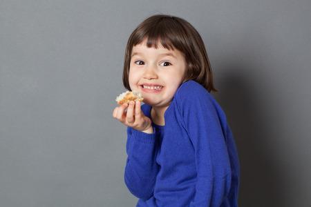 comiendo pan: cabrito diversión concepto - adorable niño en edad preescolar robar un pedazo de pan para la diversión y disfrutar de las cosas tontas, tiro del estudio