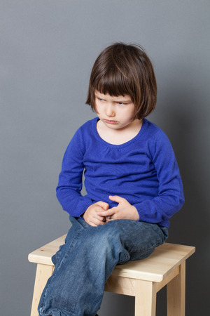 discipline: kid attitude concept - moody 4-year old child sulking on a stool for discipline or calming down in the corner for bad behavior,studio shot