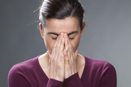 desilusion: concepto decepción - tristes 30s mujer ocultar su dolor y confusión en sus manos, tiro del estudio Foto de archivo