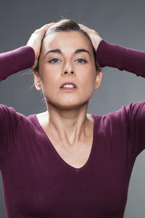 decepci�n: concepto decepci�n - Mujer de 30 a�os decepcionados que cubre su cabeza con las manos para pesar, la confusi�n y la desilusi�n, tiro del estudio