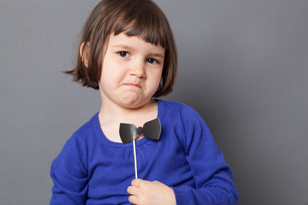 dressing up: fun kid glasses concept - unhappy female preschool child disliking holding a fake black bow tie for retro dressing up,studio shot