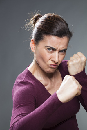 intimidate: female self-defense concept - aggressive 30s woman provoking violence in fighting and showing her fists in foreground,studio shot