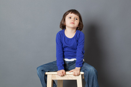 annoyed girl: kid attitude concept - angry 4-year old child sulking on a stool for discipline or calming down in the corner for bad behavior,studio shot