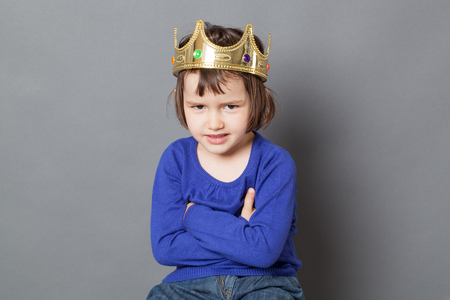 messy hair: spoiled kid concept - fun 4-year old child with messy hair and golden crown on head sitting with arms folded for mollycoddled metaphor,studio shot Stock Photo