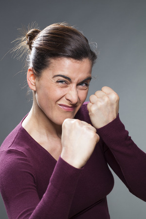 one female: female self-defense concept - bullying 30s woman impressing in creasing her eyes,fighting or provoking,studio shot