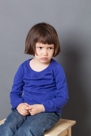 discipline: kid attitude concept - thinking 4-year old child sulking on a stool for discipline or calming down in the corner for bad behavior,studio shot