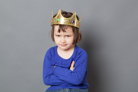 messy hair: spoilt kid concept - smiling 4-year old child with messy hair and golden crown on head sitting with arms crossed for mollycoddled metaphor,studio shot Stock Photo
