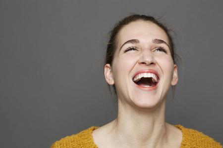 gloeiend geluk concept - mooie jaren '20 meisje barst in lachen voor welzijn en sereniteit, studio geschoten op een grijze achtergrond