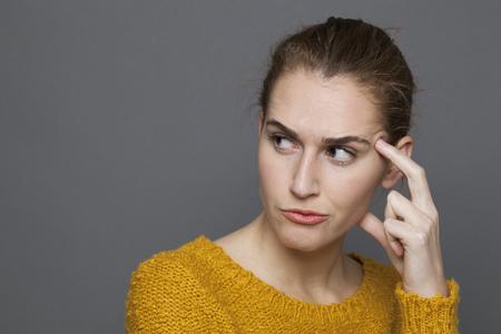 duda y la confusión concepto - retrato de la chica de 20 años molesto hermosas en la reflexión, en busca de soluciones, tiro del estudio sobre fondo gris