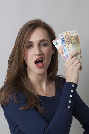 arrogancia: concepto de rentabilidad - Retrato de hermosa mujer 20s con billetes de Euro insolentes para la libertad financiera o de nuevo empleo, tiro del estudio Foto de archivo