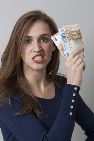 20s: value for money concept - furious 20s woman holding Euro bills for claiming earnings or economic frustration,studio shot Stock Photo