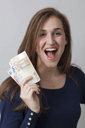 libertad: concepto de rentabilidad - magnífico retrato de la mujer 20s con billetes de Euro emocionado por la libertad financiera o ganar el premio, tiro del estudio