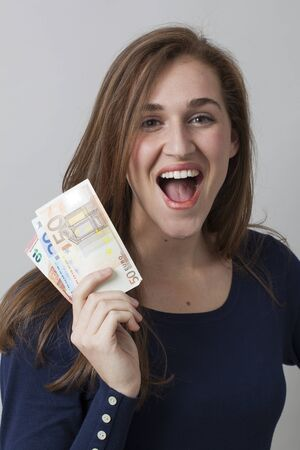 financial freedom: value for money concept - portrait of thrilled gorgeous 20s woman holding Euro bills for financial freedom or winning prize,studio shot
