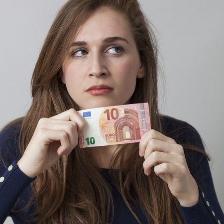 value for money concept - thinking 20s woman holding a Euro bill looking away for financial ambition,studio shot