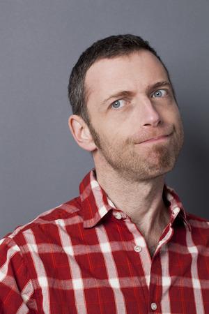 desconfianza: juzgar concepto mental - 40s decepcionado hombre que llevaba camisa casual pensar con recelo y desconfianza, tiro del estudio Foto de archivo