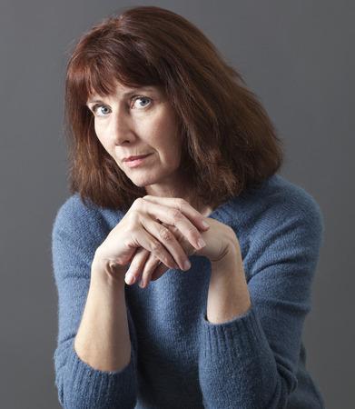 desconfianza: juzgar concepto mental - 50 sospechosos mujer que expresa la desconfianza y la reflexi�n con gesto de mano en silencio, tiro del estudio