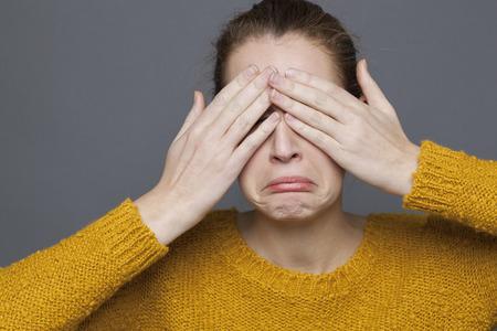 ojos llorando: sentimientos negativos concepto - retrato de la chica de 20 a�os que cubre sus ojos tristes, llorando por un problema de expresi�n, tiro del estudio sobre fondo gris