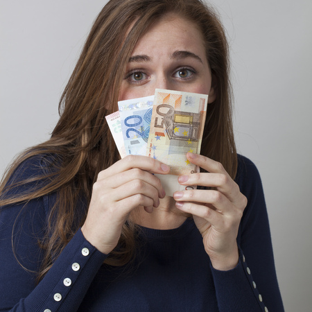 intimidated: value for money concept - scared 20s woman hidden behind Euro bills with financial ambition or intimidated by money,studio shot