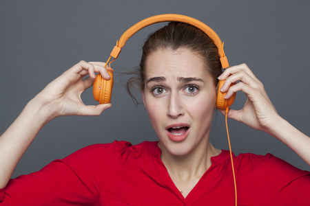 loud music: noisy headphones concept - beautiful 20s girl listening to loud music with earphones on,removing her earphones to avoid tinnitus,studio shot Stock Photo