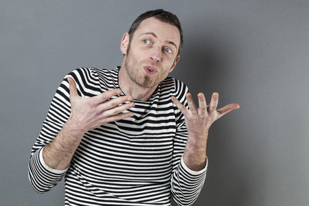 40s: body language concept - talkative 40s man enjoying discussing with expressive himself with fun hand gesture,studio shot on gray background