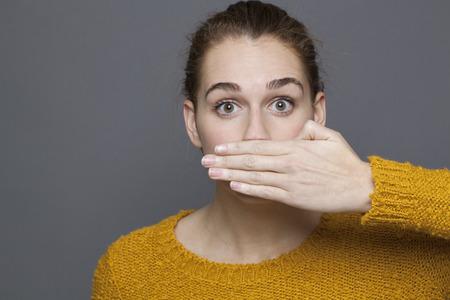 negatieve gevoelens concept - portret van verbaasd mooie jaren '20 meisje die haar mond gag metafoor, studio-opname op een grijze achtergrond