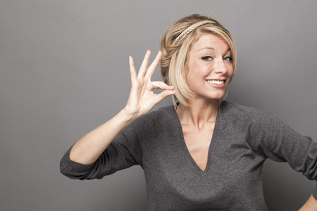 body language concept - smiling 20s blond woman making the sign of a tiny, small product with her hands,studio shot on gray background Фото со стока - 49067025