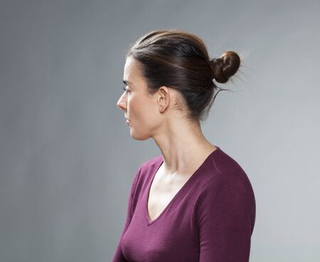 copy space: female portrait - thinking 30s woman with tied brown hair looking back for questions and nostalgia on her past,profile view,studio shot Stock Photo