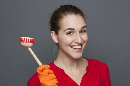obsessive: fun cleaning concept - attractive 20s girl holding a dish brush with pride for efficient and satisfying housekeeping,studio shot