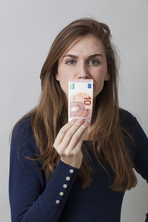 sniffing: value for money concept - frowning 20s woman sniffing a Euro bill for financial bad odor or dirty money laundering,studio shot