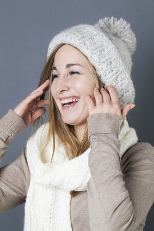 giggling: trendy warm winter - giggling young blond girl getting warmer with white wool winter scarf and hat enjoying softness and comfy fashion