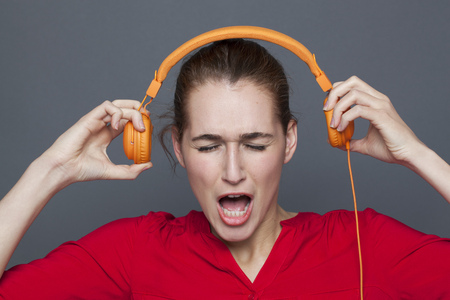 loud music: tinnitus headphones concept - shouting 20s girl listening to loud music with earphones on,removing her earphones to avoid nightmare,studio shot Stock Photo