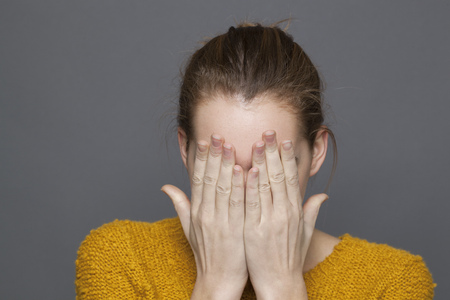 young adult women: negative feelings concept - portrait of upset 20s girl covering her face with both hands for sadness or frustration,studio shot on gray background Stock Photo