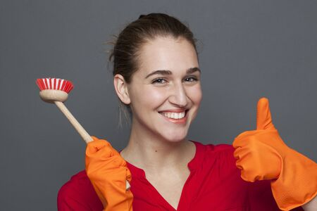 20s: fun cleaning concept - beautiful 20s girl holding a dish brush with thumb up for efficient and satisfying housekeeping,studio shot