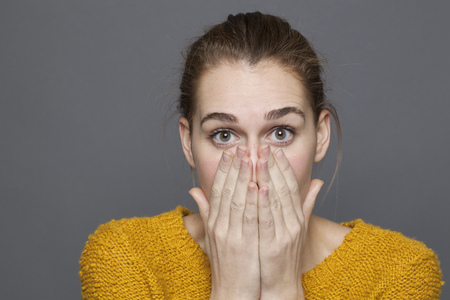 shocked: negative feelings concept - shocked beautiful 20s girl covering her mouth and nose with hands for emotions or bad odor,studio shot on gray background