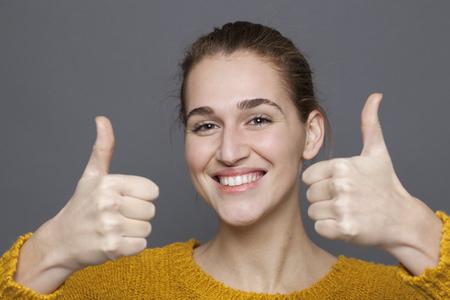 concepto de la aprobación radiante - niña de 20 años preciosa y sonriente con los pulgares dobles para arriba para la satisfacción y el éxito, tiro del estudio sobre fondo gris Foto de archivo