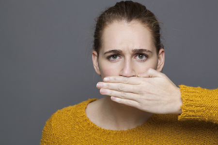 hands covering face: negative feelings concept - portrait of displeased beautiful 20s girl covering her mouth for problem of expression,studio shot on gray background Stock Photo