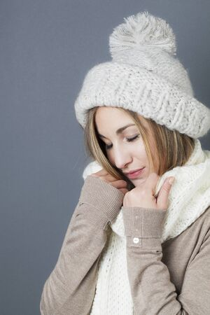 closing eyes: trendy warm winter - smiling young blond girl getting warmer with white wool winter scarf and hat closing eyes for softness and comfy fashion Stock Photo