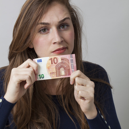 disappointed: value for money concept - displeased 20s woman holding a Euro bill disappointed by financial return on investment,studio shot