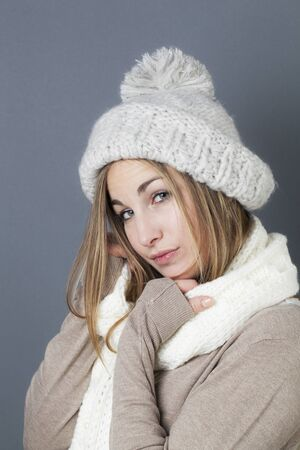 warmer: trendy warm winter - thinking young blond girl getting warmer with white wool winter scarf and hat enjoying softness and comfy fashion Stock Photo