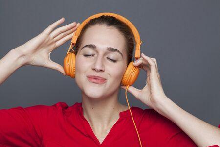 gorgeous: trendy headphones concept - gorgeous 20s girl savoring relaxing music with earphones on,studio shot
