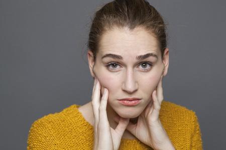 desconfianza: duda y la confusi�n concepto - retrato de esc�ptica chica hermosa de 20 a�os que expresa la desconfianza y confusi�n, tiro del estudio sobre fondo gris
